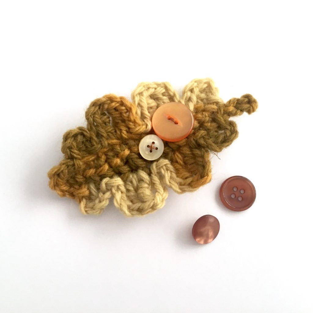 Crocheted oak leaf brooch in shades of green, brown and gold
