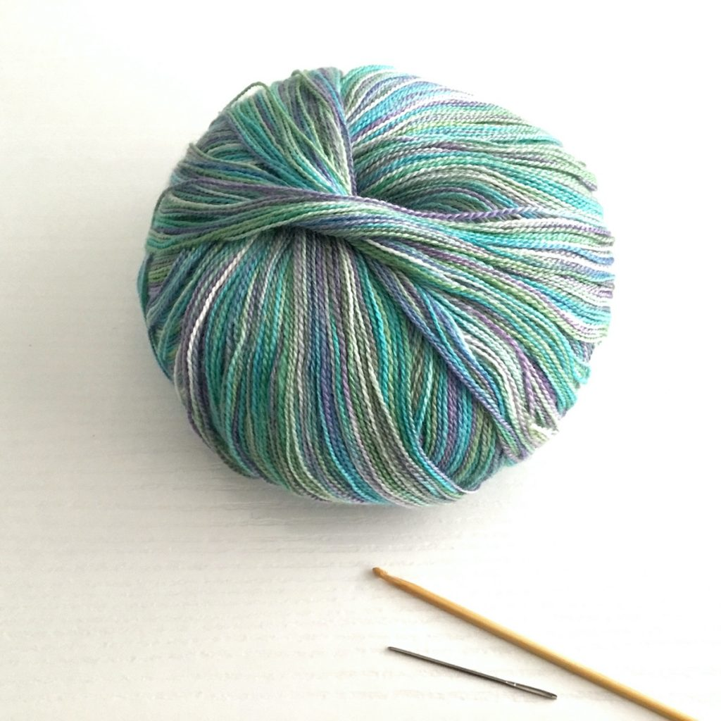 A ball of Juniper Moon Findley Dappled lace weight yarn in Grapevine 141