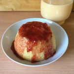 Steamed pudding with strawberry jam and custard in a jug