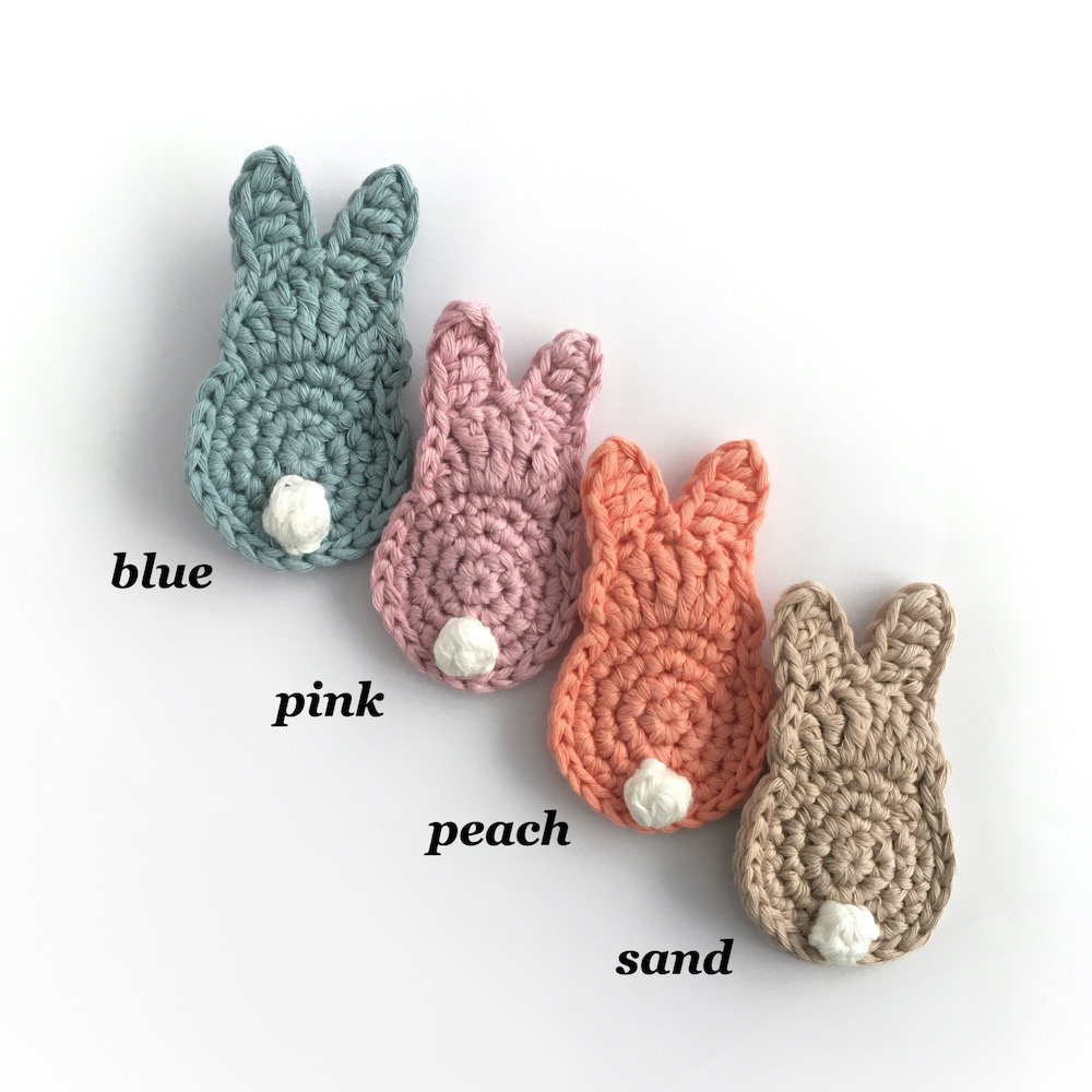 Crocheted bunny brooches in a range of colours.