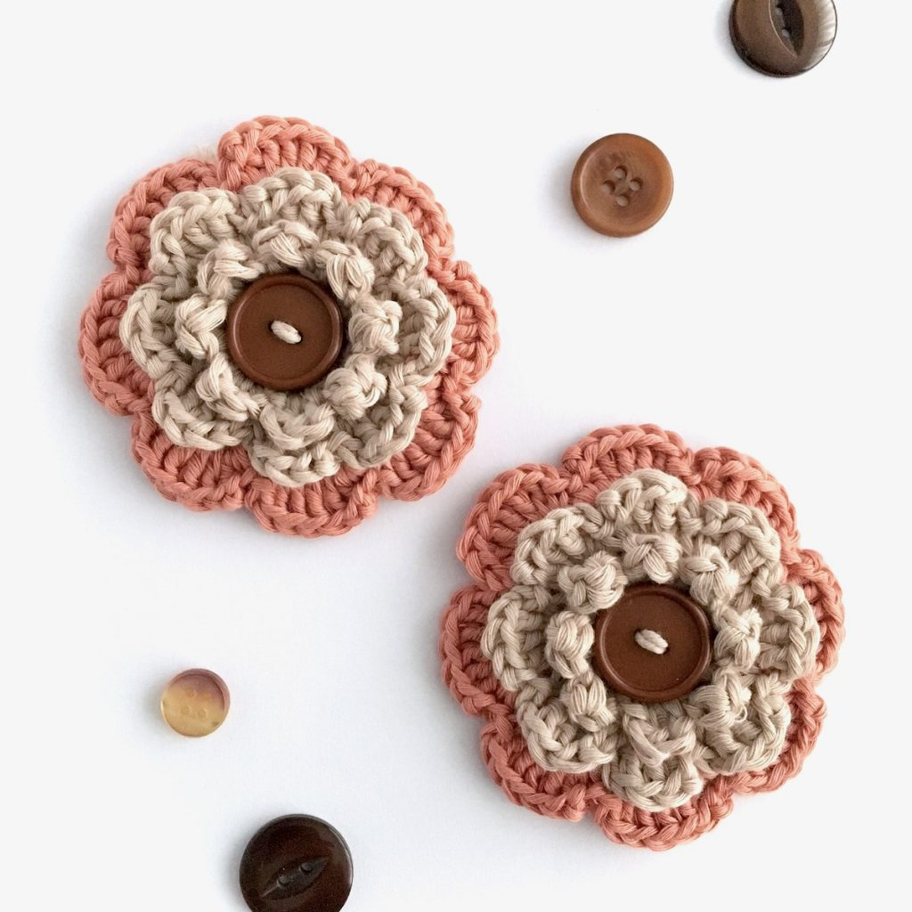 Hand-crocheted brooches with buttons from the Little Conkers Brooches with Benefits range